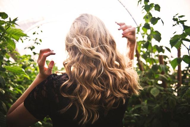 vitamina para unha e cabelo mulher loira mexendo no cabelo