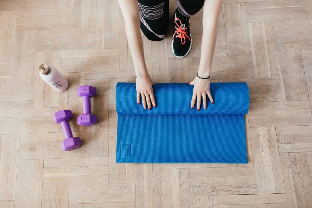 suplementação para hipertrofia mulher com tapete de yoga e pesos